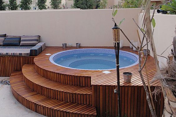 Inground tile hot tub wrapped in wood