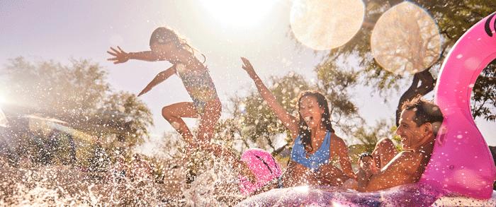 Family enjoying summer pool fun splashing and on floats