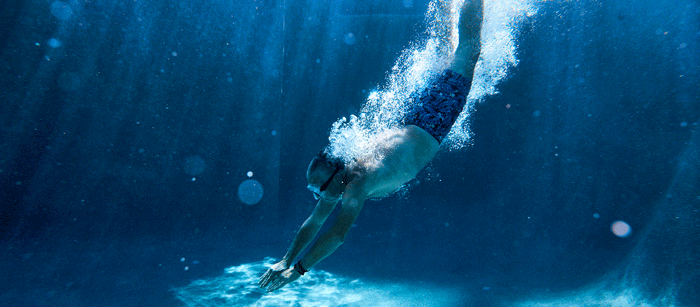 Underwater angle of man diving into a pool