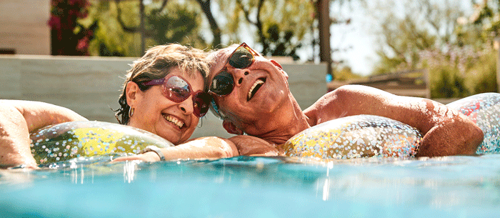 Senior couple relaxing in a pool on floats
