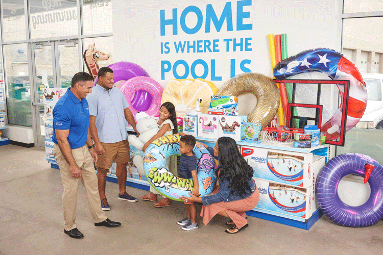 Leslie's associate helping a family find fun pool floats, toys, and games