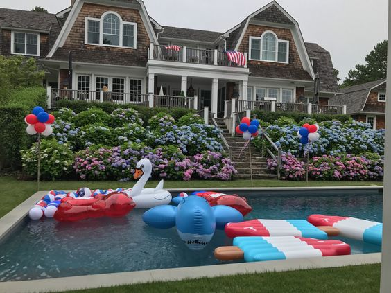 USA flags waving and red, white and blue floats and decorations in and around pool