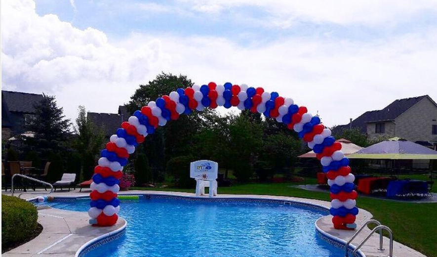 Patriotic red, white and blue balloon archway over pool